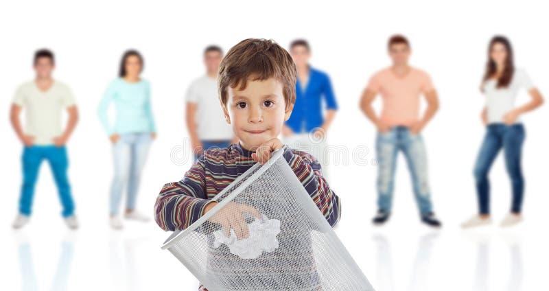 Lustiges Kind, das eine Rolle im Behälter mit jungen Leuten wirft stockbild