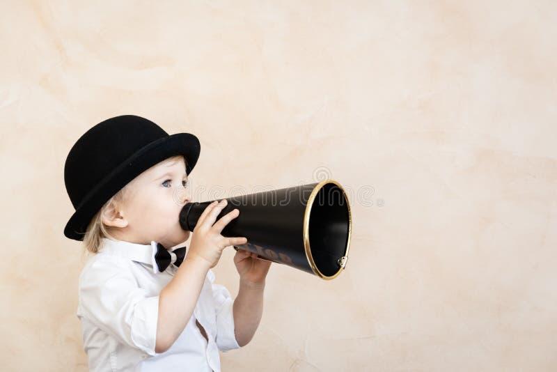 Lustiges Kind, das mit schwarzem Retro- Megaphon spielt lizenzfreie stockfotos