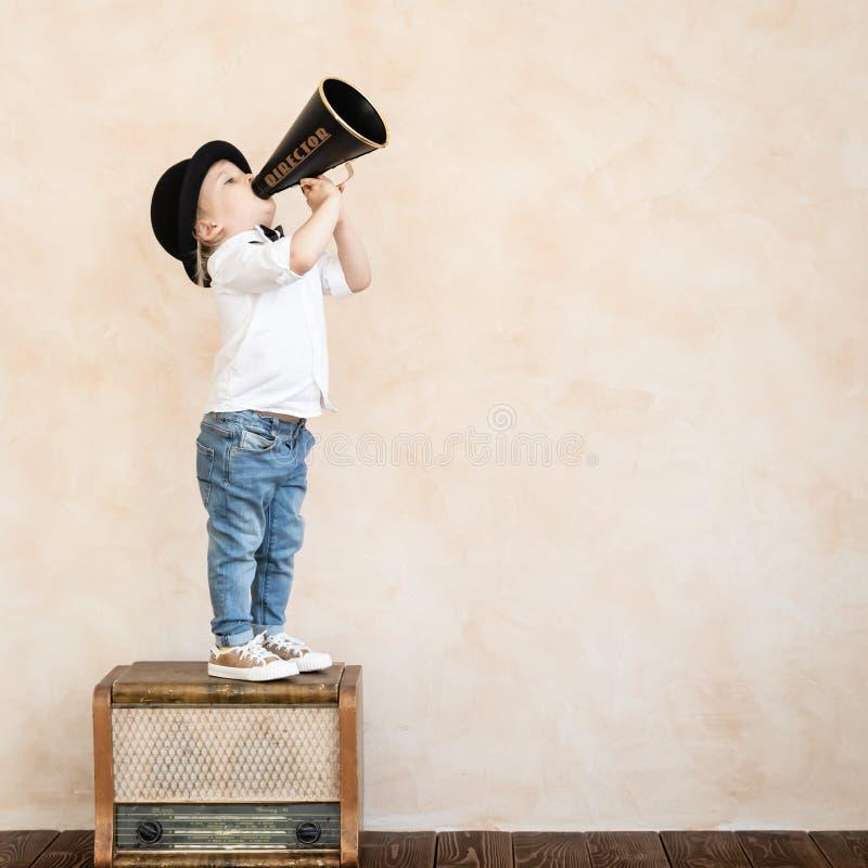 Lustiges Kind, das mit schwarzem Retro- Megaphon spielt stockbild
