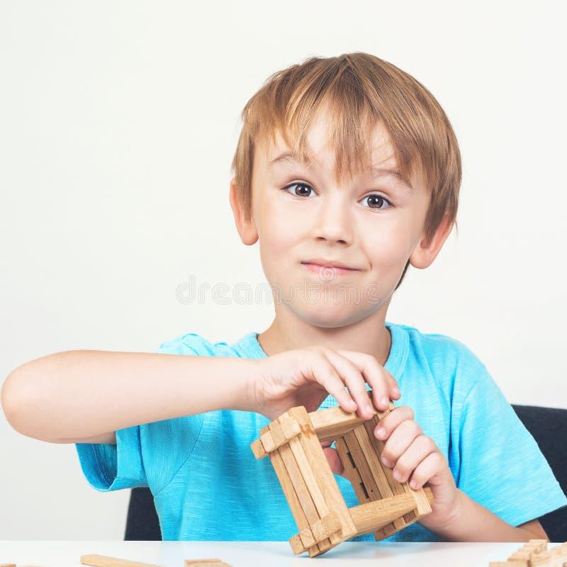Lustiges Kind errichtet kleines Holzhaus Eco Haus Goldtasten in den Fingern mit Häusern Wenig Jungenspiele mit Blöcken Kindheit u lizenzfreie stockbilder