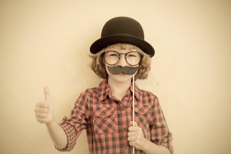 Lustiges Kind mit dem gefälschten Schnurrbart stockfoto
