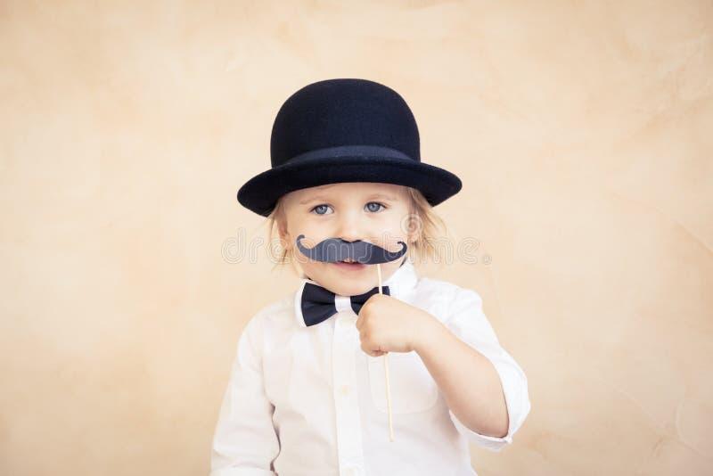 Lustiges Kind mit dem gef?lschten Papierschnurrbart lizenzfreies stockfoto