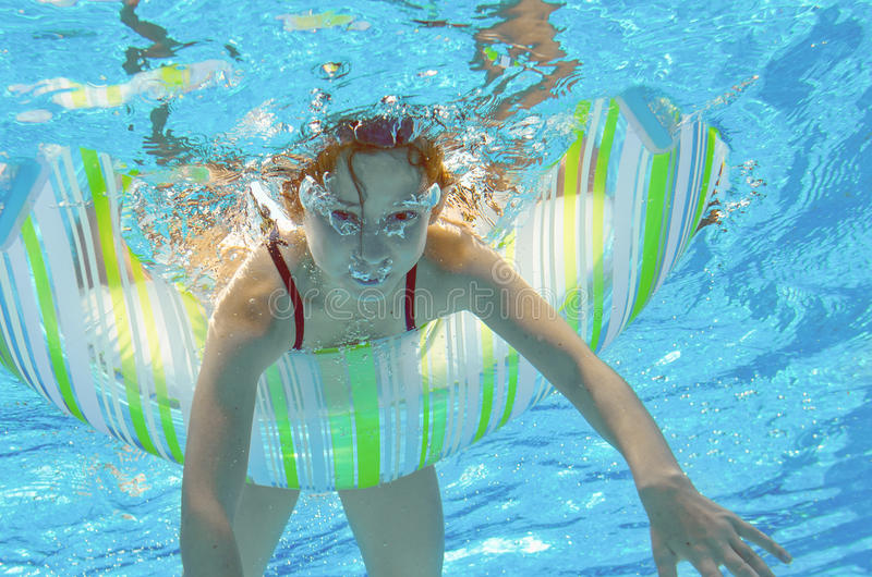 Lustiges Kind schwimmt im Pool unter Wasser, das Kind, das Spaß hat und im Urlaub mit Gummiring, kleines Mädchen spielt stockfotografie