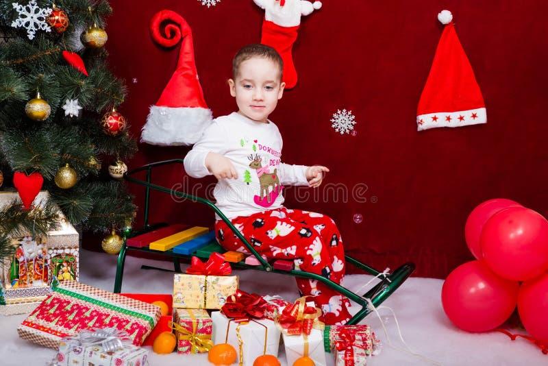 Lustiges Kind sitzt auf einem Pferdeschlitten nahe bei einem Weihnachtsbaum stockfotografie