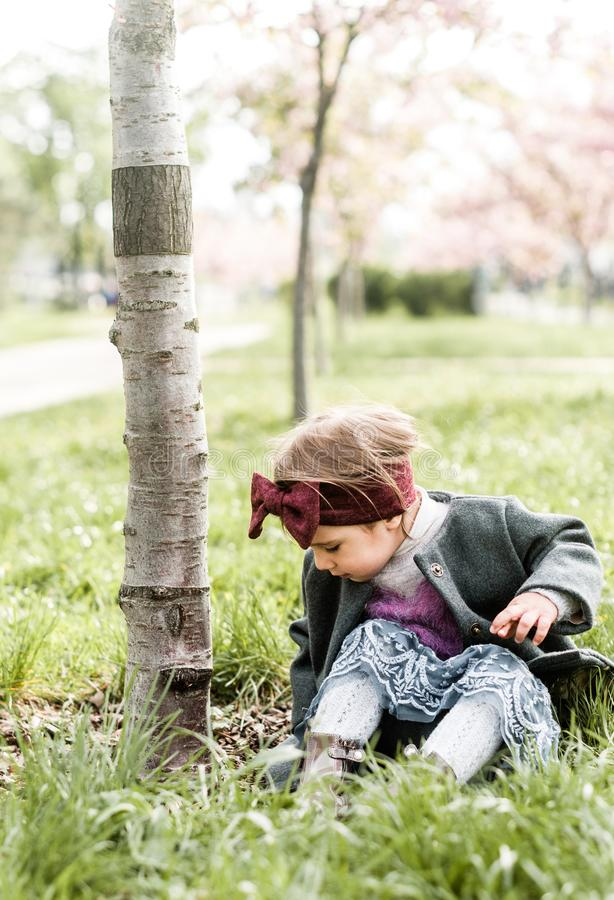 Lustiges Kindermädchen überprüft Insekten auf einem Baumstamm im Park stockfoto