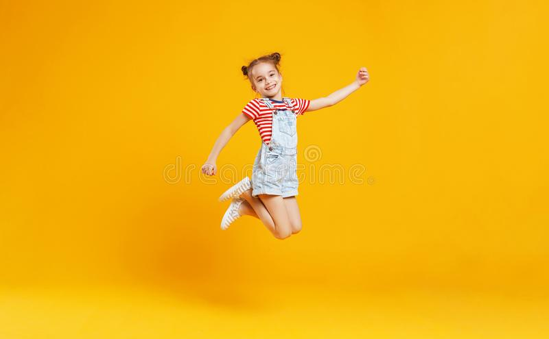 Lustiges Kindermädchen, das auf farbigen gelben Hintergrund springt stockbild