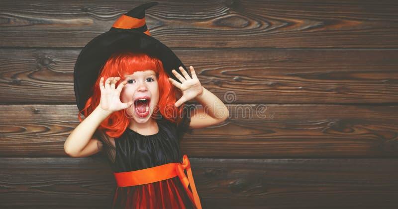 Lustiges Kindermädchen im Hexenkostüm für Halloween erschrickt stockbilder