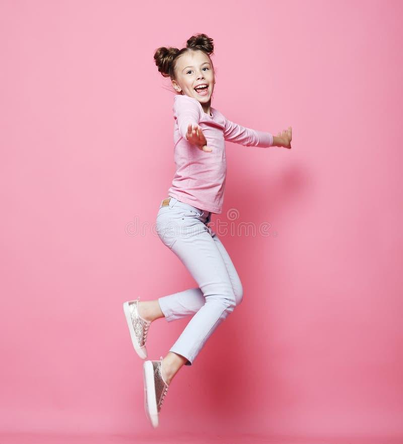 lustiges Kindermädchen kleidete das zufälliges Springen auf rosa Hintergrund stockbilder