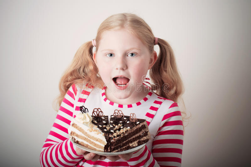 Lustiges Kindermädchen mit Kuchen stockfoto