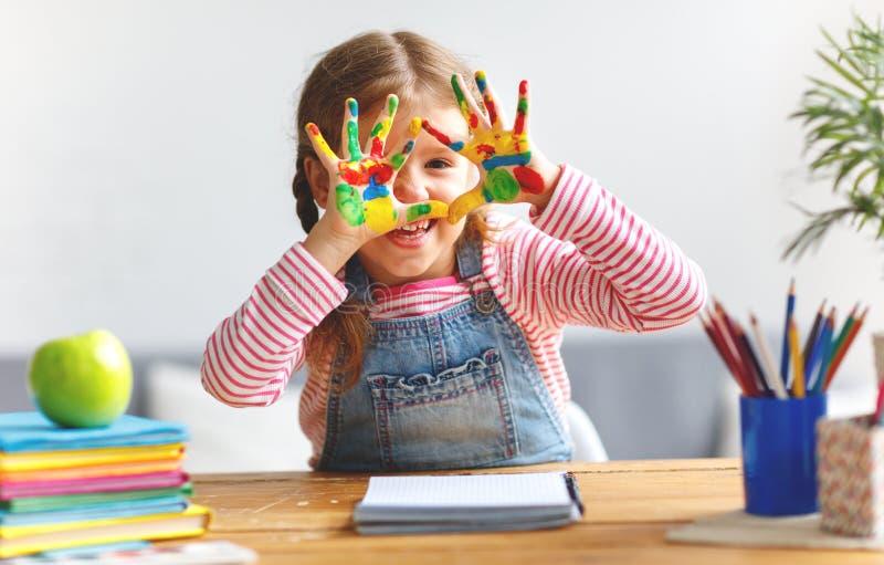 Lustiges Kindermädchen zeichnet die lachenden Showhände, die mit Farbe schmutzig sind stockfotografie