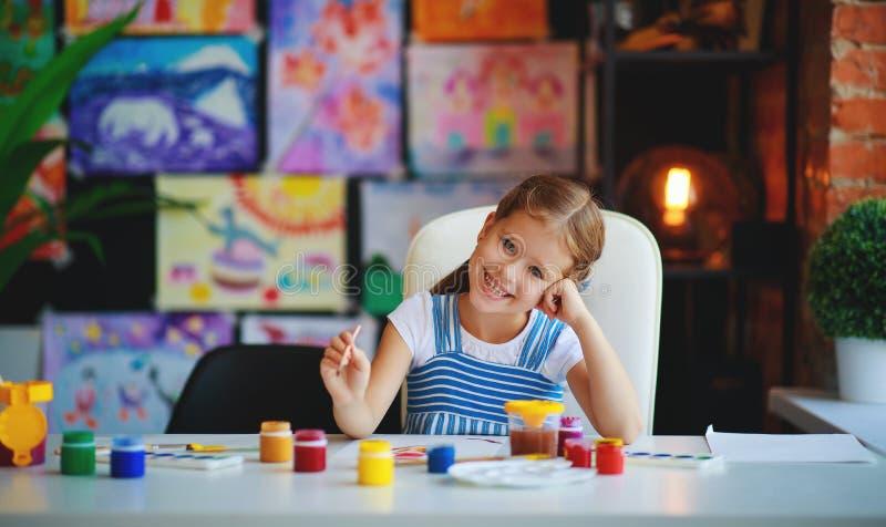 Lustiges Kinderm?dchen zeichnet die lachenden Showh?nde, die mit Farbe schmutzig sind stockfotografie