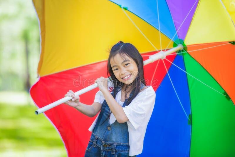 Lustiges kleines asiatisches Mädchen mit Regenschirm lizenzfreie stockbilder