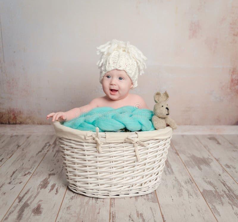 Lustiges kleines Baby, das im Korb sitzt lizenzfreies stockbild