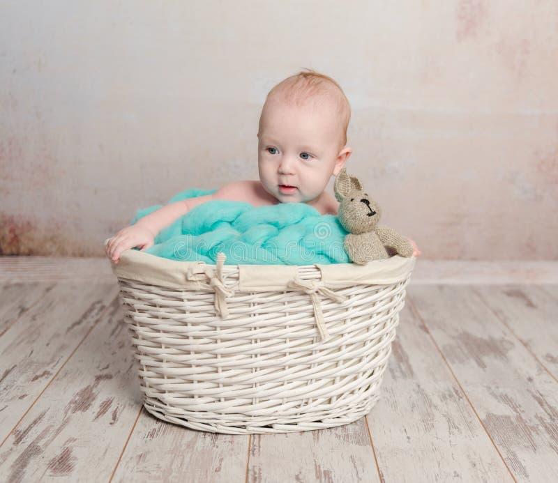 Lustiges kleines Baby, das im Korb sitzt stockfotografie