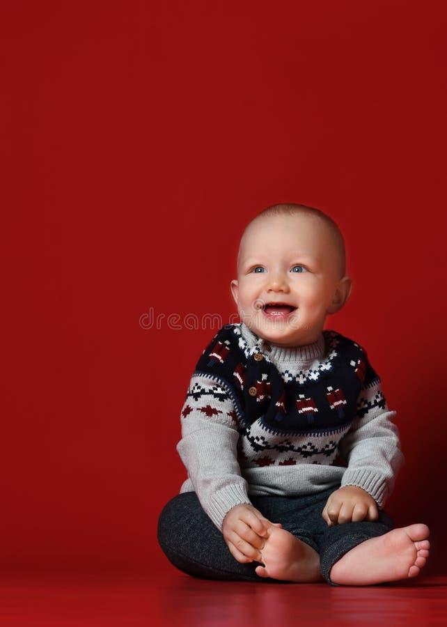 Lustiges kleines Baby, das warme gestrickte Weihnachtsstrickjacke am Studio am kalten Wintertag trägt lizenzfreie stockfotos