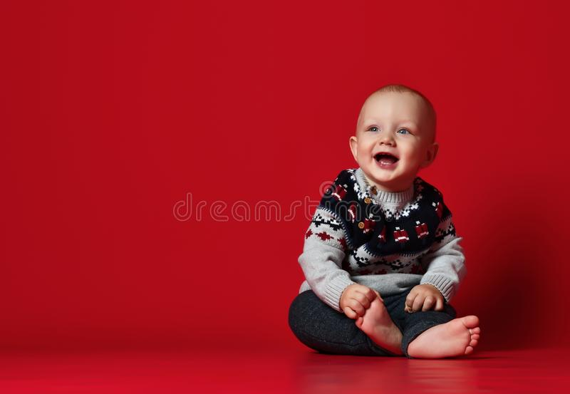 Lustiges kleines Baby, das warme gestrickte Weihnachtsstrickjacke am Studio am kalten Wintertag trägt stockfotos