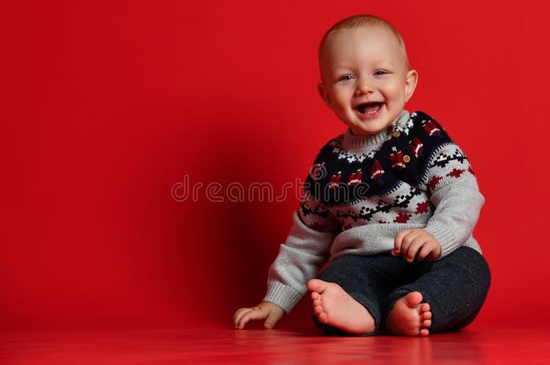 Lustiges kleines Baby, das warme gestrickte Weihnachtsstrickjacke am Studio am kalten Wintertag trägt lizenzfreie stockfotografie