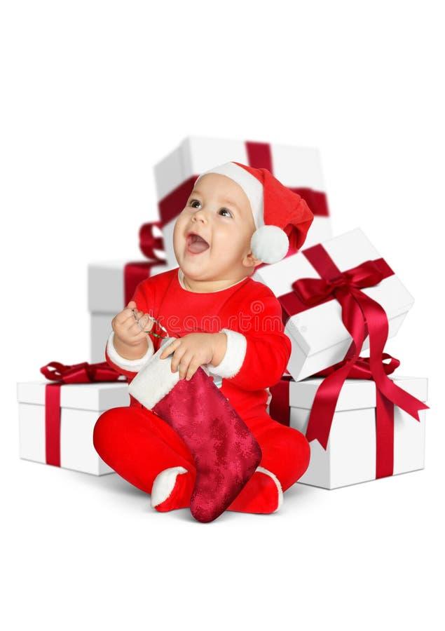 Lustiges kleines Baby Santa Claus mit den Weihnachtsgeschenken lokalisiert auf w lizenzfreie stockfotografie