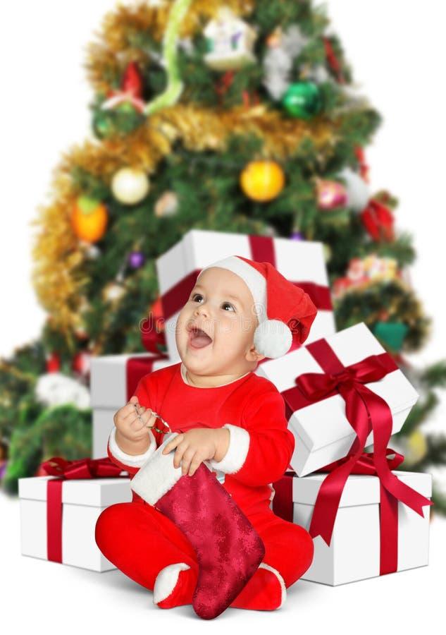 Lustiges kleines Baby Santa Claus mit Weihnachtsgeschenken auf Weiß stockbilder