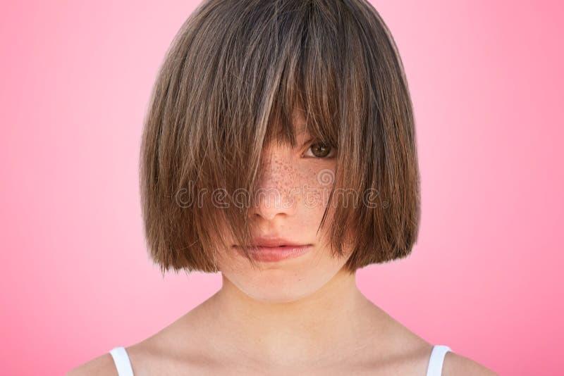 Lustiges kleines Kind bedeckt Gesicht mit dem Haar, demonstriert ihre neue Frisur, sich fühlt wie wirkliches Modell, aufwirft geg stockfotografie