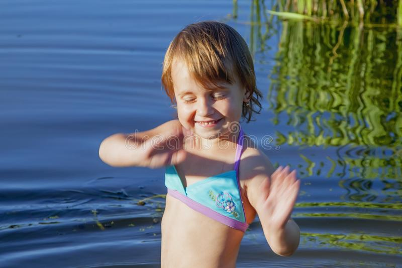 Lustiges kleines Kindermädchen steigen in das Wasser des Sees ein zu schwimmen H stockbilder