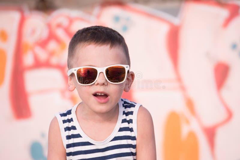 Lustiges kleines Kindertragende Sonnenbrille und -hemd auf Graffitihintergrund lizenzfreie stockbilder