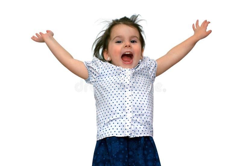 lustiges kleines lächelndes Mädchen springt und zeigt Finger Atelieraufnahme auf wei?em Hintergrund stockbild