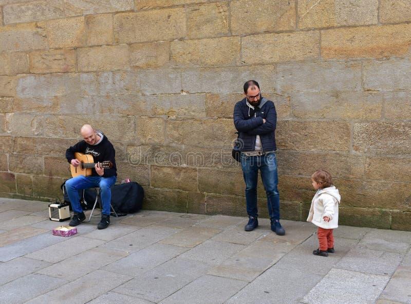 Lustiges kleines Mädchen und Mann, die Gitarre in einer Straße nah an Kathedrale spielt Santiago de Compostela, Spanien, am 22. F lizenzfreies stockbild