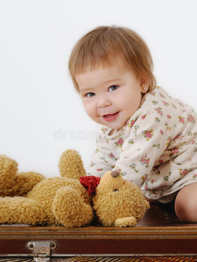 Lustiges kleines Mädchen, das auf einem Koffer spielt lizenzfreies stockbild
