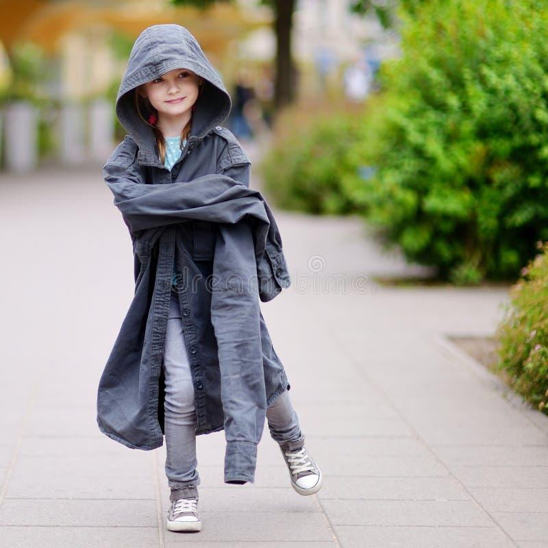 Lustiges kleines Mädchen, das den Mantel ihrer Väter trägt stockfotografie