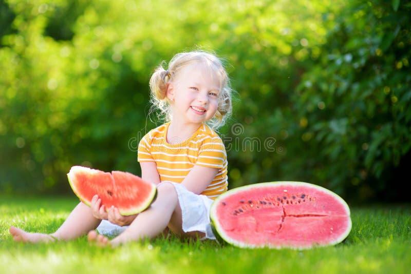 Lustiges kleines Mädchen, das draußen Wassermelone isst stockbild