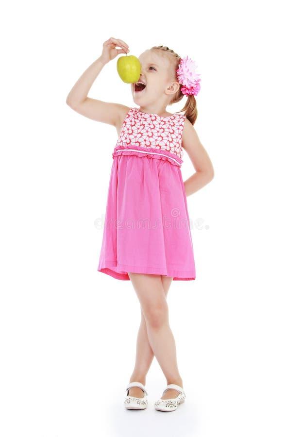 Lustiges kleines Mädchen, das einen Apfel isst lizenzfreies stockbild