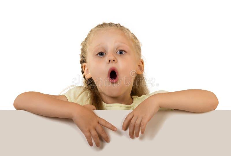 Lustiges kleines Mädchen, das hinter dem Plakat lokalisiert auf Weiß steht stockfotografie