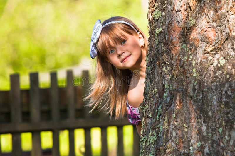 Lustiges kleines Mädchen, das im Park spielt lizenzfreies stockbild