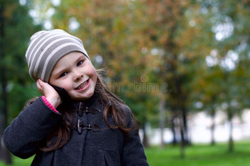 Lustiges kleines Mädchen, das mit einem Handy spricht stockbild