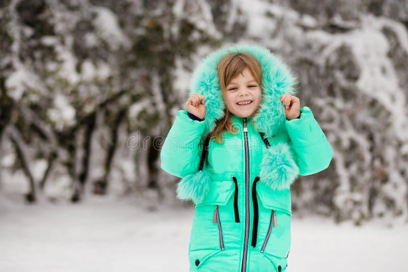 Lustiges kleines Mädchen, das Spaß im schönen Winterpark hat lizenzfreie stockbilder