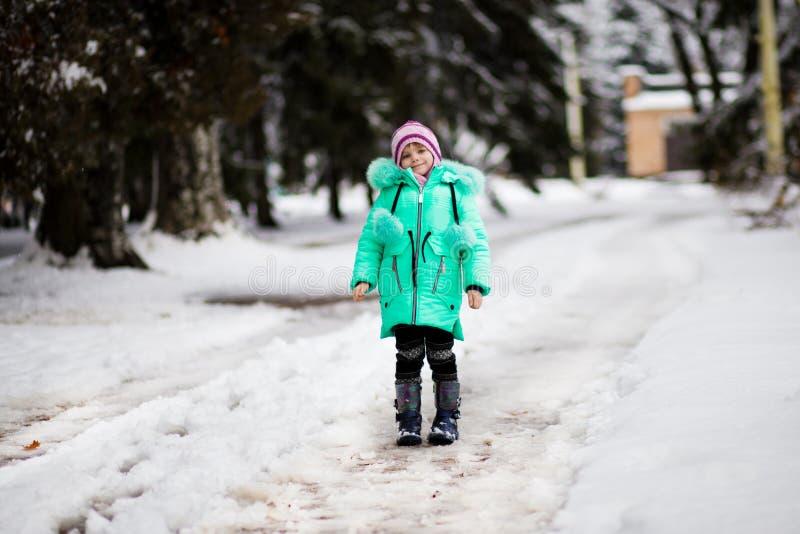 Lustiges kleines Mädchen, das Spaß im schönen Winterpark hat stockbilder