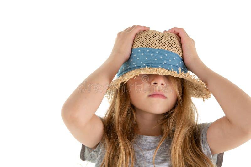 Lustiges kleines Mädchen, das unter ihren Strohhut sich versteckt stockbild
