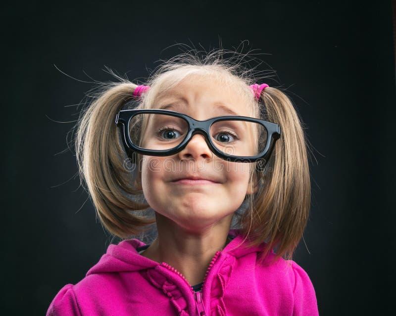 Lustiges kleines Mädchen in den lustigen großen Schauspielen stockfotografie