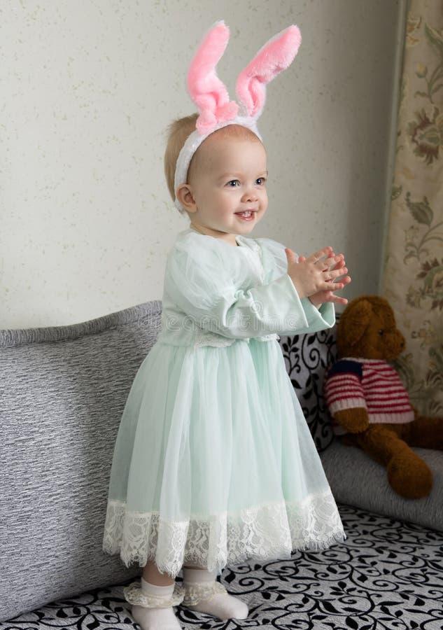 Lustiges kleines Mädchen in einem Stirnband mit den Häschenohren klatscht ihre Hände und Lachen stockbild