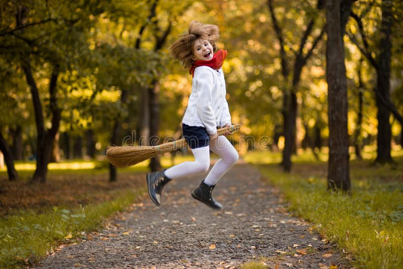 Lustiges kleines Mädchen fliegt auf Besen im Herbst stockfotos
