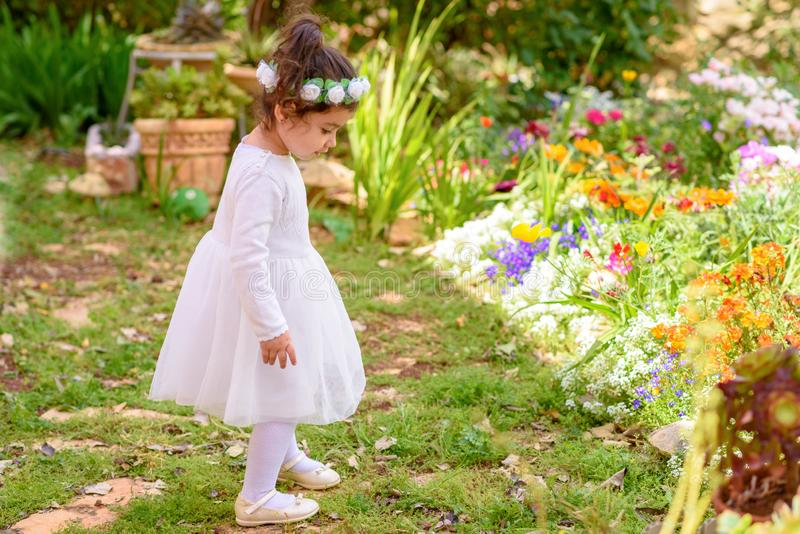 Lustiges kleines Mädchen im weißen Kleider- und Blumenkranz, der Spaß ein Sommergarten hat lizenzfreie stockbilder