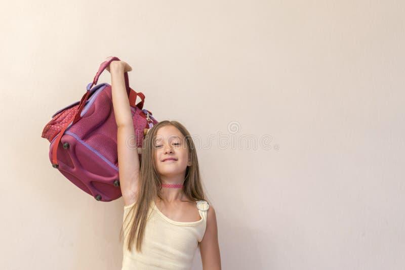 Lustiges kleines Mädchen mit dem großen Rucksack, der Spaß gegen weiße Wand springt und hat Auf schwarzem Hintergrund mit copyspa stockbilder