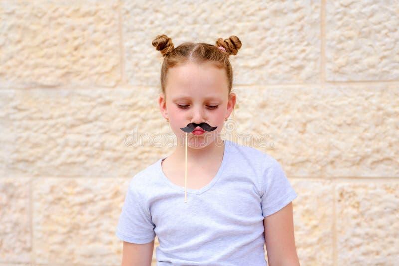 Lustiges kleines Mädchen mit den Papierschnurrbartkarnevalsmasken, die Spaß auf weißem Wandhintergrund haben lizenzfreies stockfoto