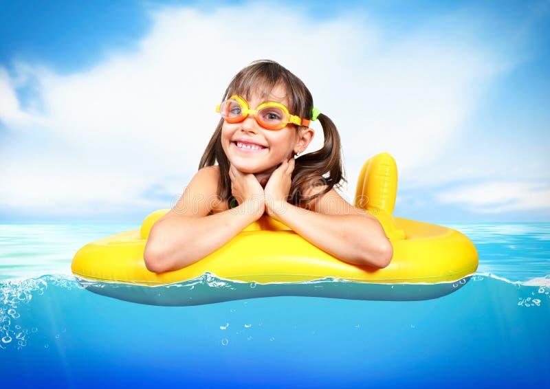 Lustiges kleines Mädchen mit den tauchenden Gläsern, die aufblasbaren Ring a schwimmen lizenzfreie stockbilder