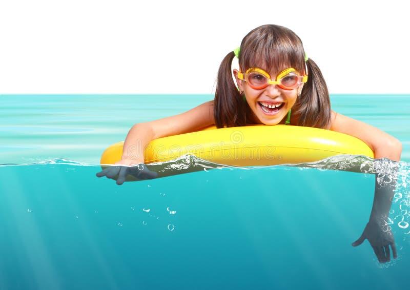 Lustiges kleines Mädchen mit den tauchenden Gläsern, die aufblasbaren Ring schwimmen, stockbild