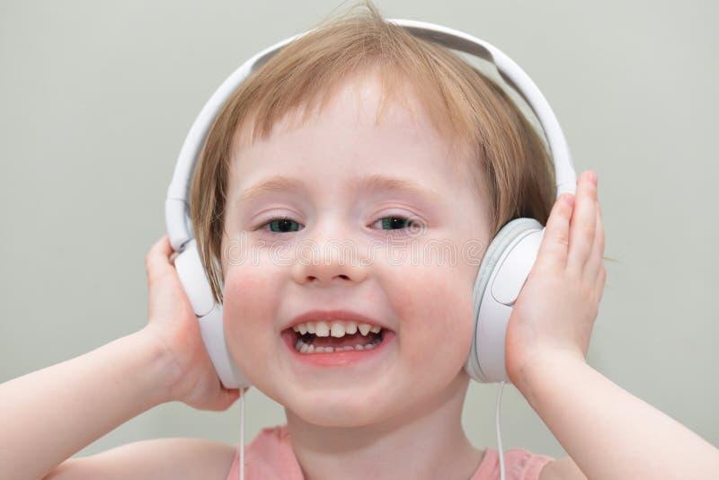 Lustiges kleines Mädchen mit Kopfhörern stockfoto