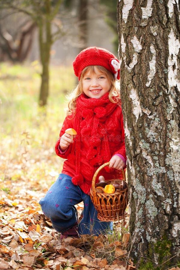 Lustiges kleines Mädchen mit Korb mit Pilzen stockfotografie