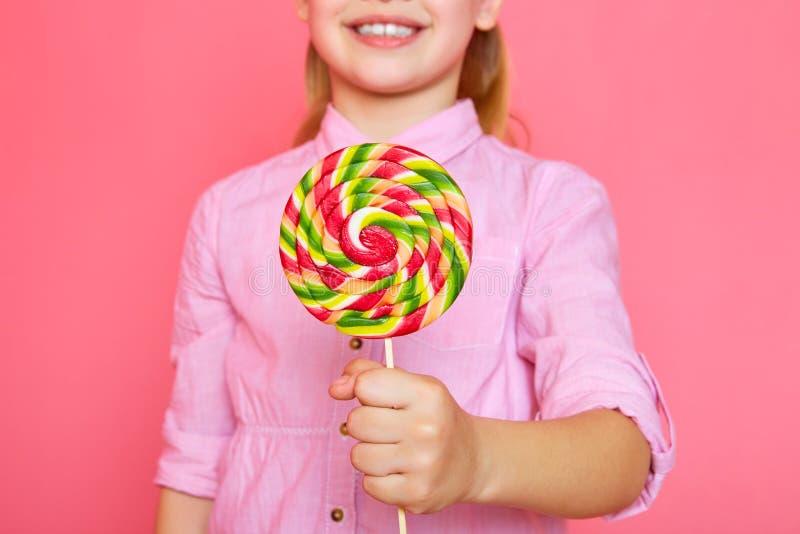 Lustiges kleines Mädchen mit Süßigkeitslutscher Glückliches kleines Mädchen, das eine Süßigkeit hält lizenzfreie stockfotos