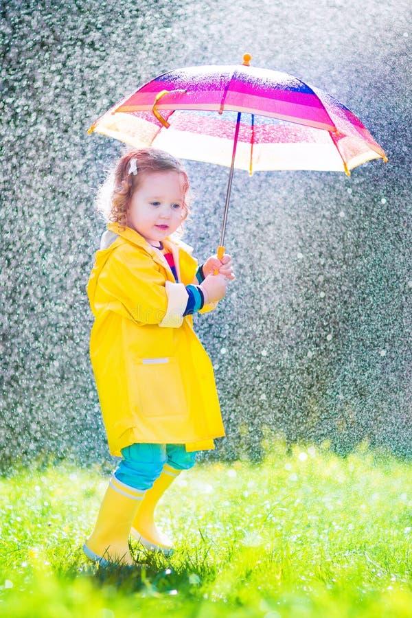 Lustiges Kleinkind mit dem Regenschirm, der im Regen spielt stockfoto